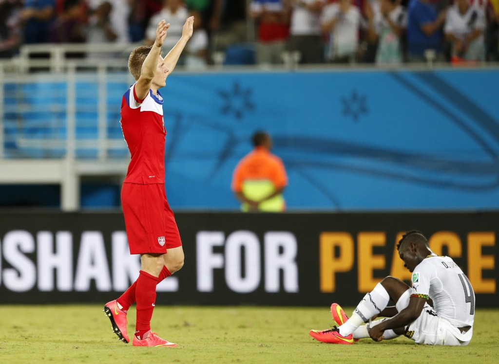 Ghana's Daniel Opare, right, sits on the pitch as United States' Aron Johannsson celebrates after his team's 2-1 victory over Ghana.