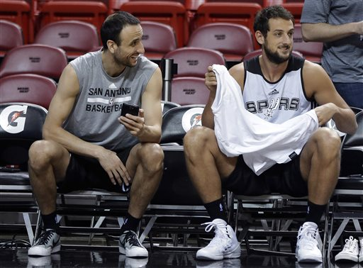 San Antonio Spurs' Manu Ginobili, left, laughs with Marco Belinelli, right, during NBA Finals basketball practice Wednesday in Miami. The Spurs lead the Miami Heat two games to one in the best of seven series. The Associated Press