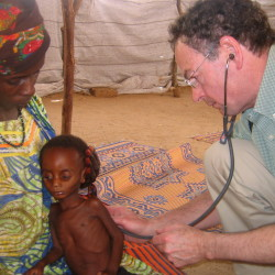 Dr. Richard Rockefeller examines a patient in Nigeria in 2009.