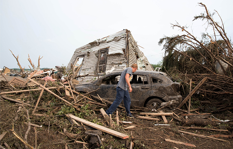 Tim Nelson  searches for survivors in Pilger, Neb.,  after the town was hit by a tornado Monday.