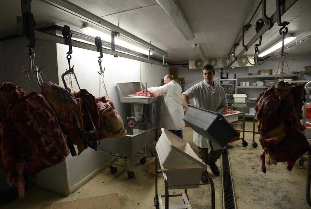 Arthur Bisson and Burt Packard process meat into hamburger.