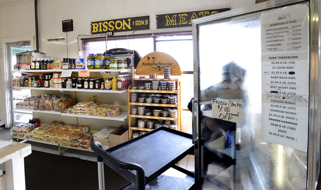 Chelsey Bisson puts ox tails in a freezer in the store at the Bisson family farm in Topsham.