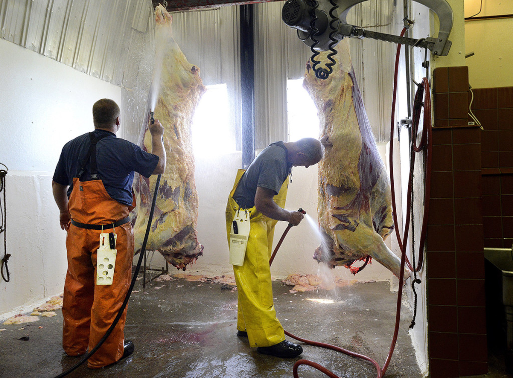 Danny Pollock and Andy Bisson wash two halves of a beef carcass in the slaughter house at the Bisson family farm.
