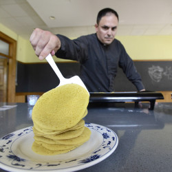 Father Dumais stacks ployes on a plate after he cooks them.