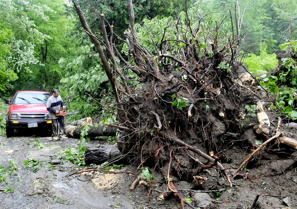 """R.G. Smith cuts up a tree that fell and blocked Osprey Lane off Corinna Road in St. Albans on Wednesday. """"I just wanted to help out friends,"""" Smith said. Power and other utilities were knocked out by a powerful storm Tuesday evening."""