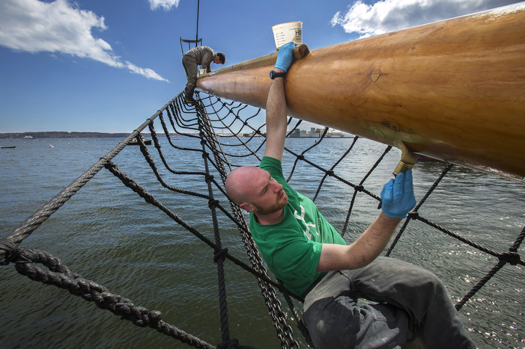Gerard Hoogeboom varnishes the bowsprit of the American Eagle at the North End Shipyard in Rockport while preparing the schooner for the sailing season. Varnishing the end of the bowsprit is Mike Foshay.