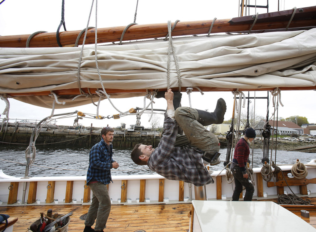 John Spencer puts his weight into tying off the main sail.