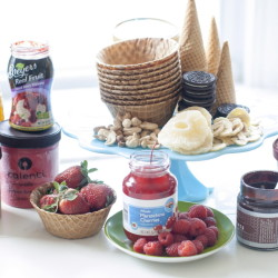 Supplies for ice cream season might include, clockwise from top center, waffle cones and bowls, Oreos, assorted nuts, dried pineapple, granola, Haagen-Dazs ice cream, chocolate sauce, raspberries, maraschino cherries, strawberries, Talenti gelato, honey and Breyers real fruit topping.