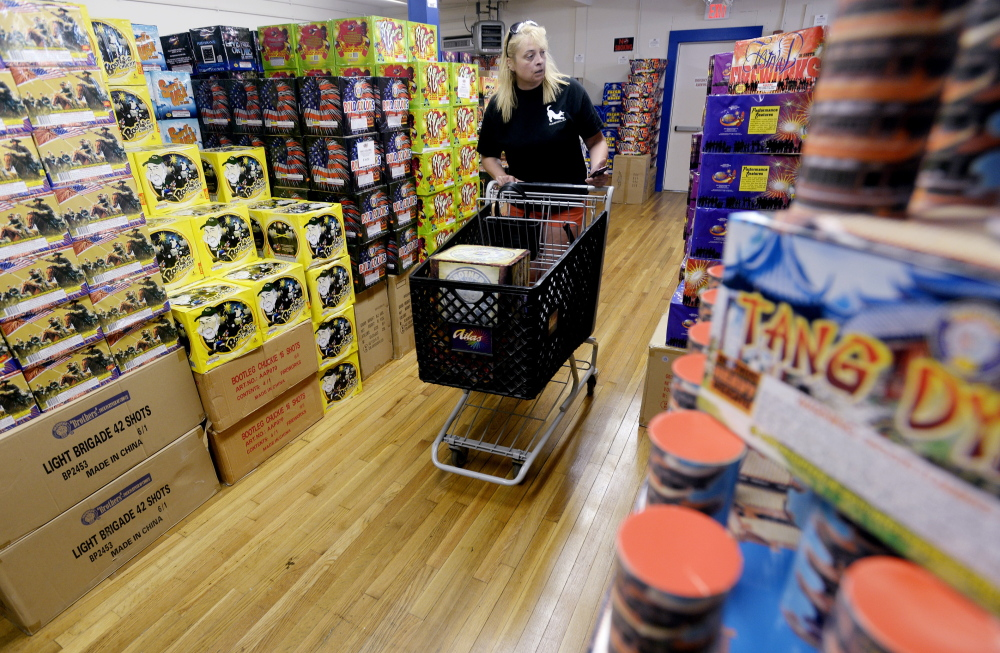 """Catherine McConnell of Lyman shops Wednesday at Atlas PyroVision in Scarborough. McConnell said she did research online before deciding what to buy for July Fourth at her family's house on Lake Arrowhead. """"We like to put on a weekend-long display,"""" she said."""