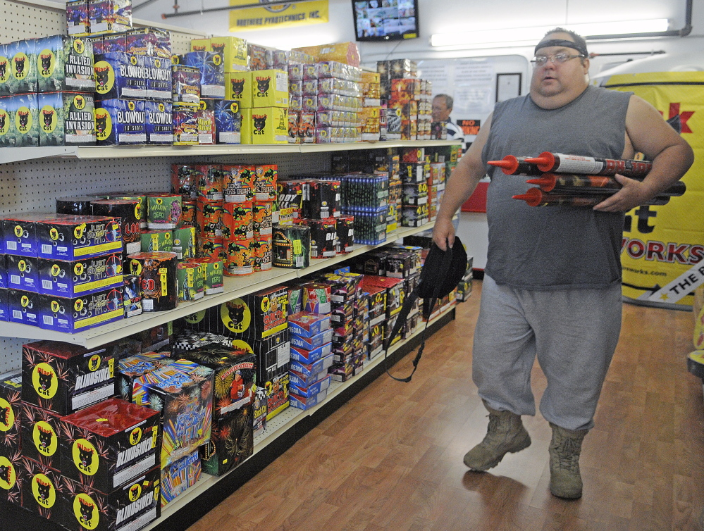 """John Bergen of Somerville carries fireworks Tuesday at the Pyro City store in Manchester. Bergen, a self-described professional explosives engineer, said safety is paramount with fireworks.  """"It's up to the individual to keep it safe so we all can enjoy the tradition,"""" he said. This year, shoppers are looking for lots of colors in their fireworks, one store official said."""