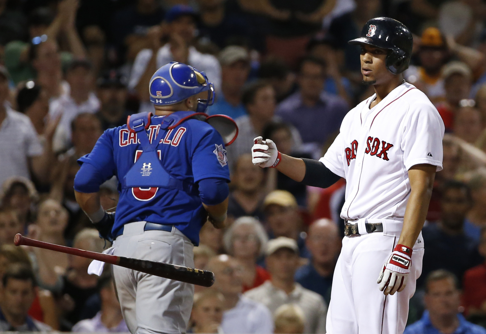 Red Sox third baseman Xander Bogaerts tosses his bat after striking out with the bases loaded in the fourth inning against the Chicago Cubs at Fenway Park on Wednesday. Cubs catcher Welington Castillo is at left.