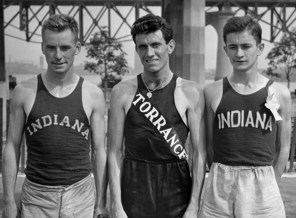 In a July 13, 1936 file photo, Don Lash of Indiana, left, Louis Zamperini of Los Angeles, center, and Thomas Deckard of Indiana, who  represented the United States in the Olympic Games in the 5,000 meter team, at the Olympic tryouts in New York. Zamperini, a U.S. Olympic distance runner and World War II hero, has died at 97.