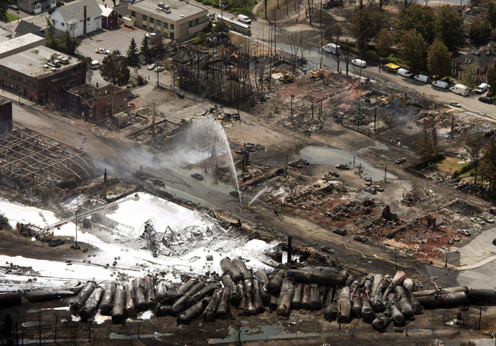 The downtown core is in ruins as firefighters water smoldering rubble in Lac-Megantic, Quebec, on July 7, 2013, a day after a train derailed, igniting tanker cars carrying crude oil.