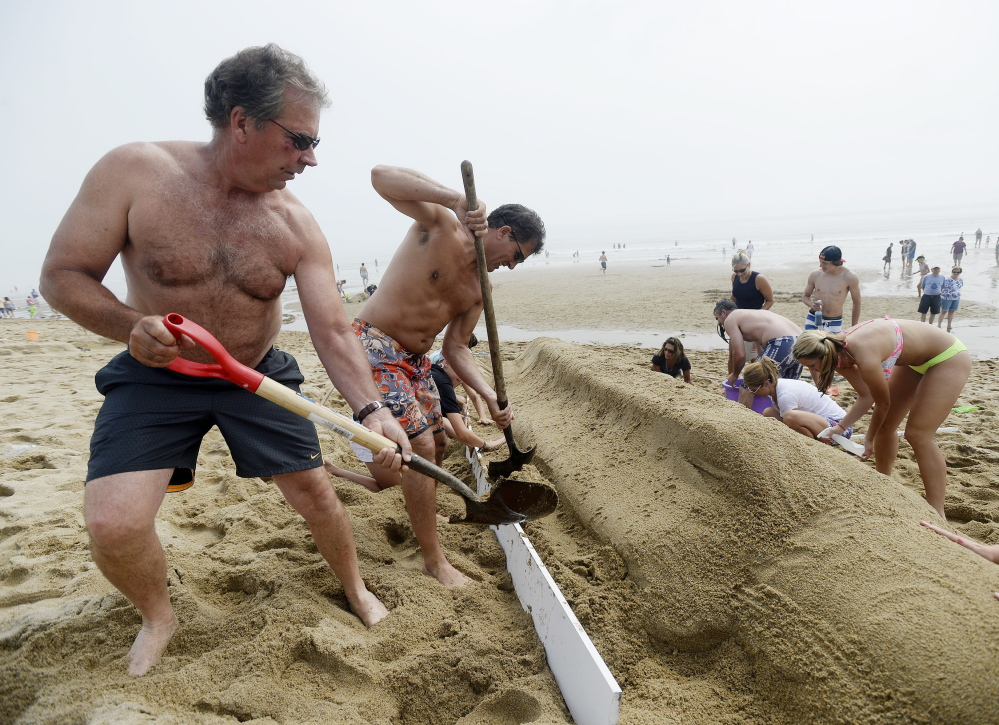 Phil Bonner of Hudson, Mass., left and Tom Curley of Stow, Mass., center, work with their team to build a sand sculpture of bottle rocket popsicle, during the competition in Ocean Park on Thursday. The team went on to win first place.