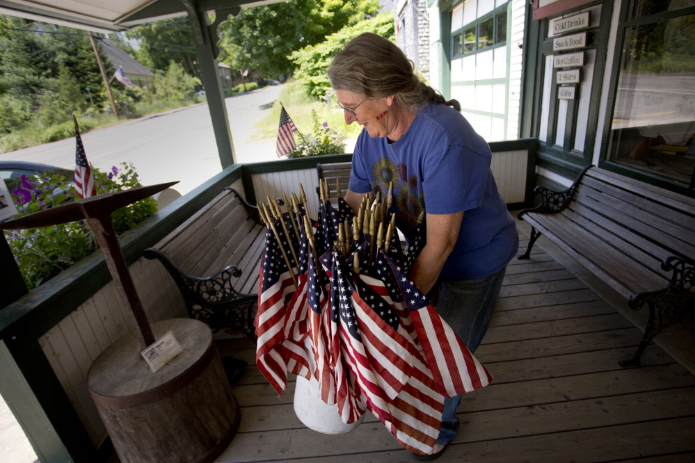 Sue Martin, an employee at Liberty Graphics in the Waldo County town of Liberty, sets out a collection of American flags, left over from the town's Memorial Day celebration, on the store's porch recently. She says she gives the flags away.