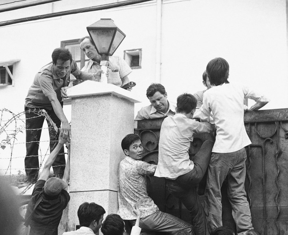 Vietnamese try to scale the U.S. Embassy wall in desperate attempts to get aboard the evacuation flights in Saigon on May 1, 1975.