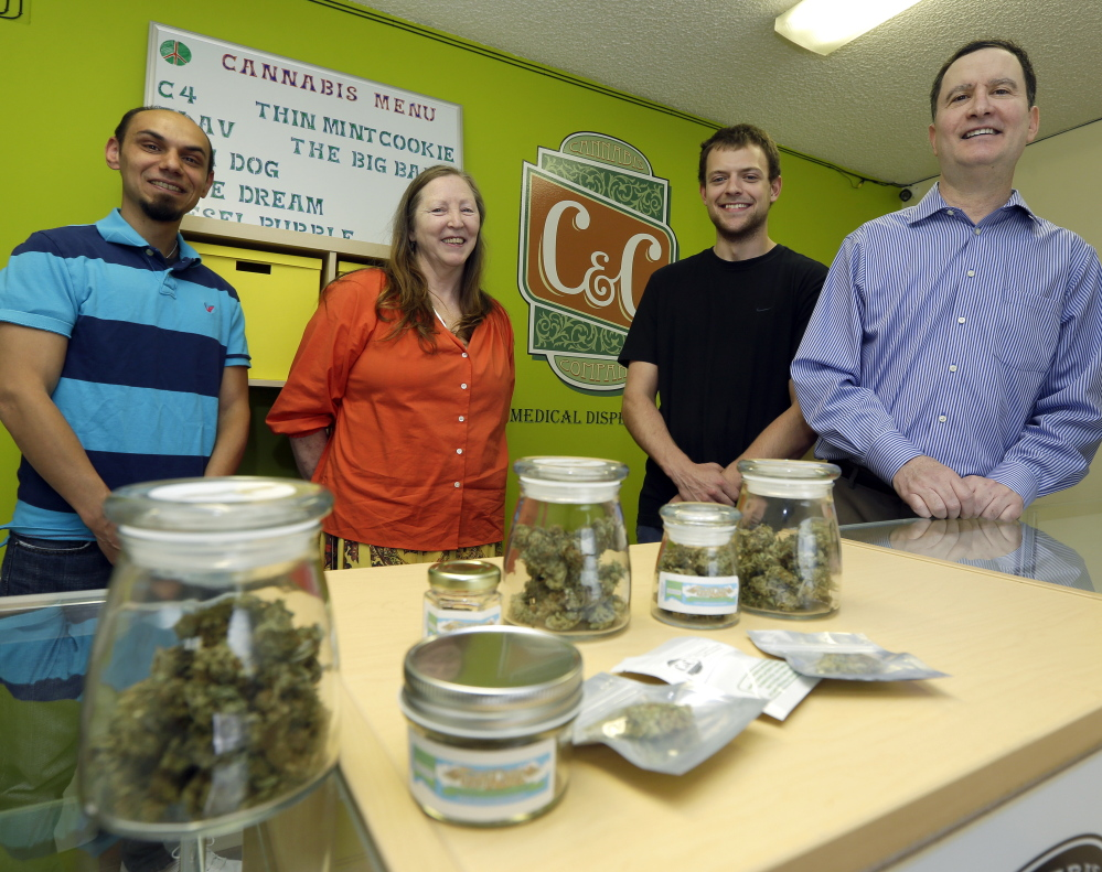 Pete O'Neil, right, stands with employees in his medical marijuana dispensary in Seattle. After he struck out in the pot-shop license lottery, he turned to Plan B – the dispensary.