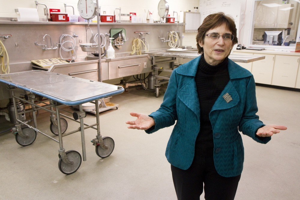 Dr. Margaret Greenwald talks about operations at the Office of the Chief Medical Examiner inside the autopsy room in Augusta in April. Greenwald retired as Maine's chief medical examiner May 30, and the office was already struggling to deal with its caseload.
