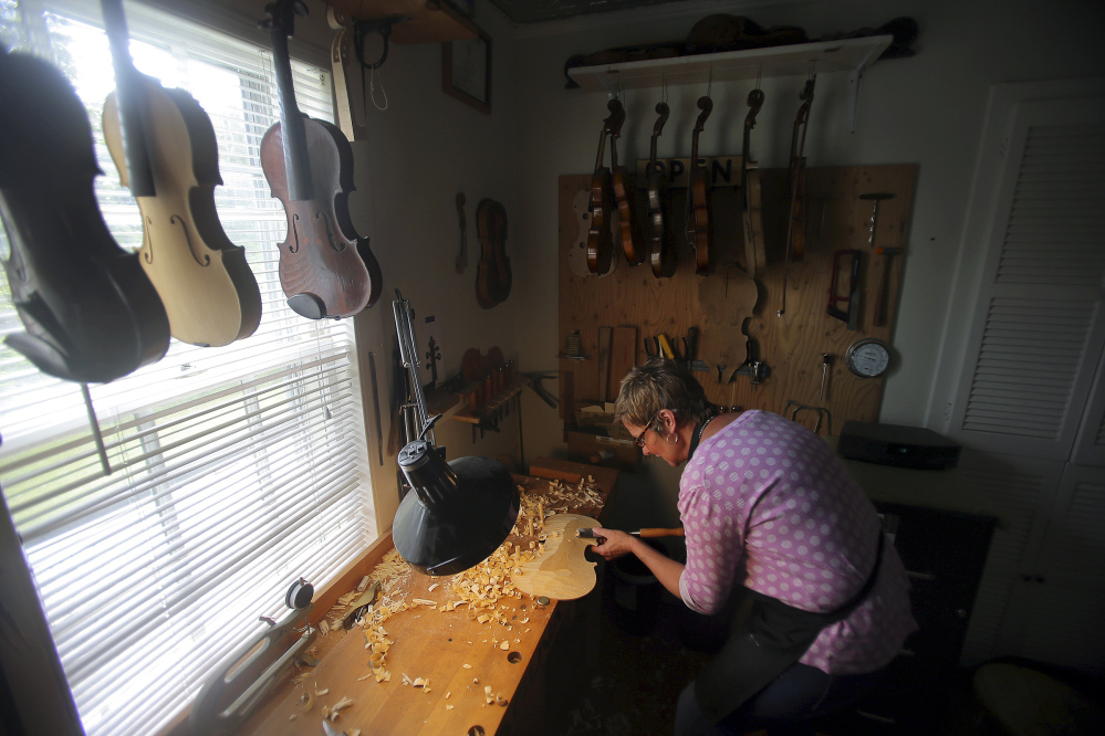 """Rose Clancy carves a flat section into a violin piece in her studio in Chatham, Mass. """"There's a real joy to making an instrument,"""" she said, """"then using it to play music."""" She founded the Chatham Fiddle Company three years ago and hosts concerts by top performers."""