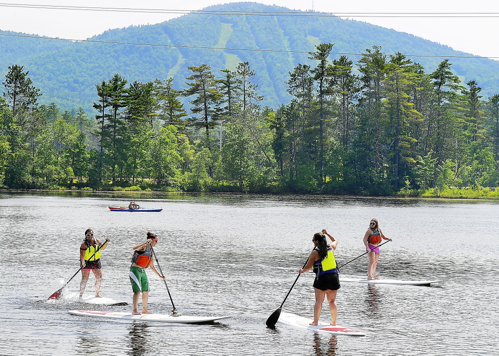 With the ski resort of Mt. Abram serving as a backdrop, paddle boarders from the Sunday River ski resort enjoy the cool waters and beautiful scenery at Round Pond and the adjacent waterways in Greenwood.
