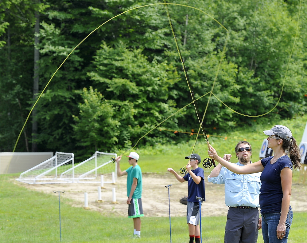 Stuart Hickey, a fly casting instructor, helps Jennifer King, right, and her sons Tyler, 15, left, and Bryson, 11, learn how to cast – one of several new offerings at the Sunday River resort in that are part of the new L.L. Bean Outdoors Discovery School there.