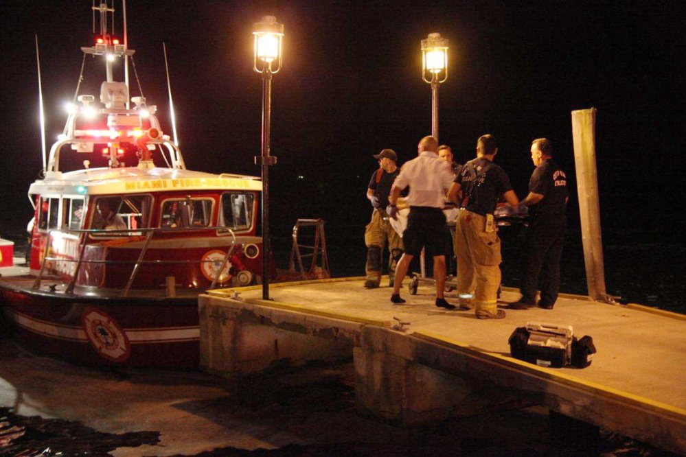 Emergency workers carry an injured person on a stretcher on Friday night after three boats collided near a Miami marina around the end of a fireworks display.