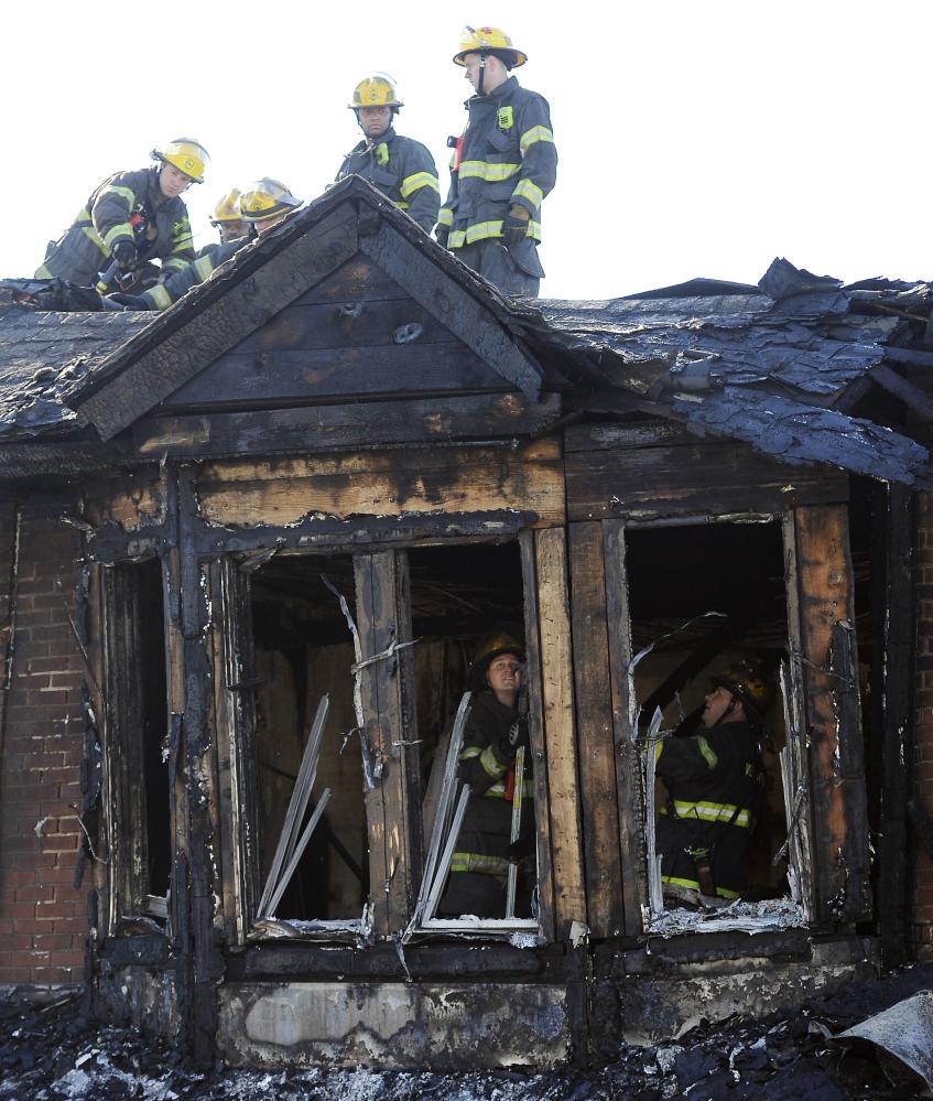 Philadelphia firefighters work on  burned row homes on Saturday in Philadelphia.