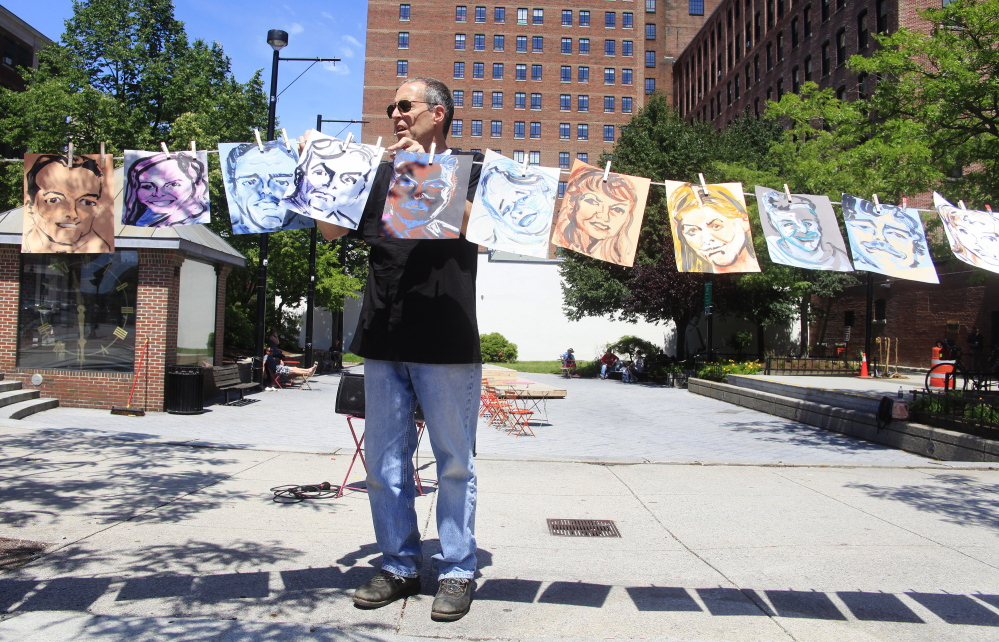 Dan Wood of South Portland helps to hang 26 portraits, painted by Lee Chisholm of Freeport, representing 26 of the 47 victims of the Lac-Megantic train disaster on Sunday, the first anniversary. Religious and environmental activists held a vigil in Congress Square Park to remember the victims of the Lac-Megantic train disaster.