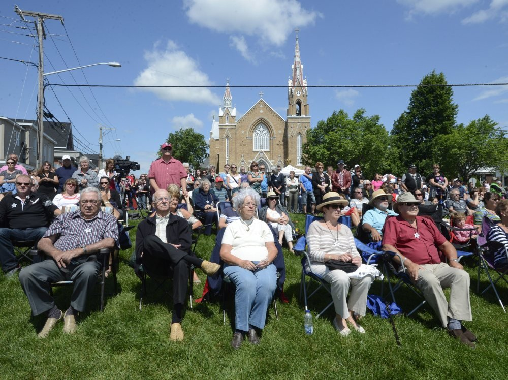 People watch a church service from outside in Lac-Megantic, Quebec, on Sunday on the first anniversary of a train derailment in the small Quebec town that killed 47 people.