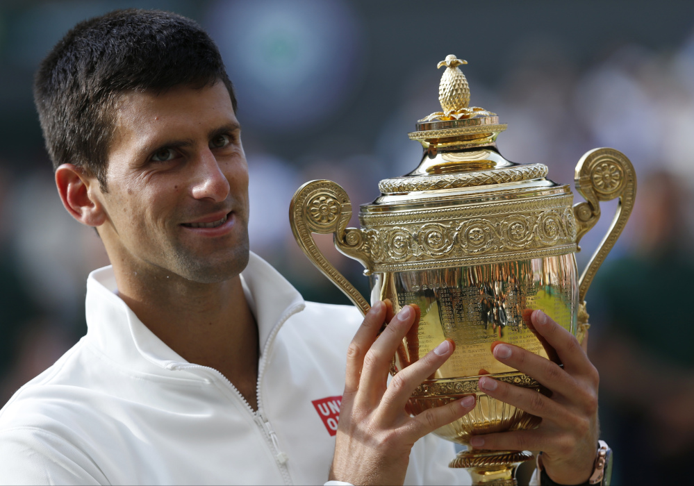 Novak Djokovic holds the trophy after defeating Roger Federer in the men's singles final at Wimbledon on Sunday.