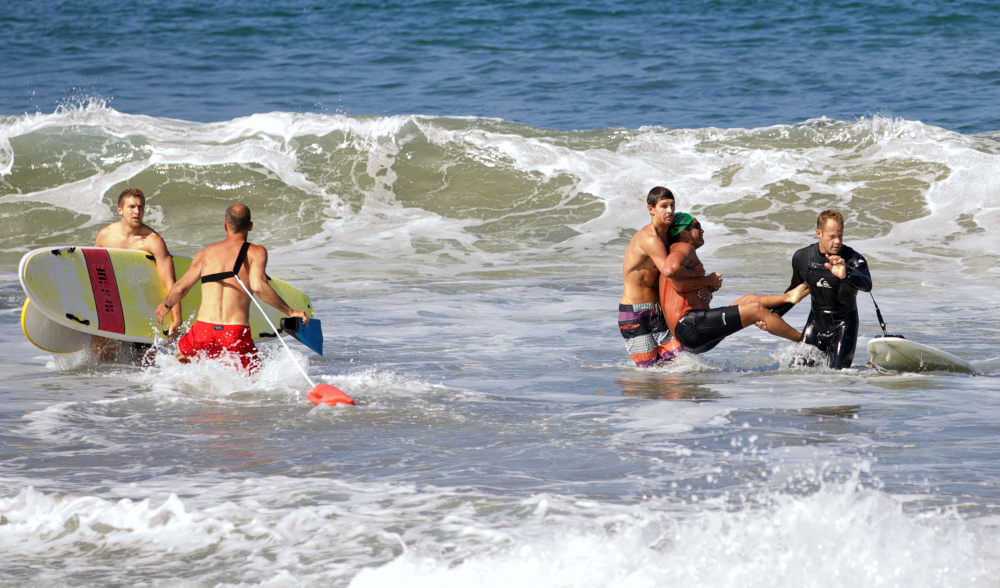 Two men carry a swimmer, second from right, after he was bitten by a great white shark, as lifeguards close in at left in the ocean off Southern California's Manhattan Beach on Saturday.