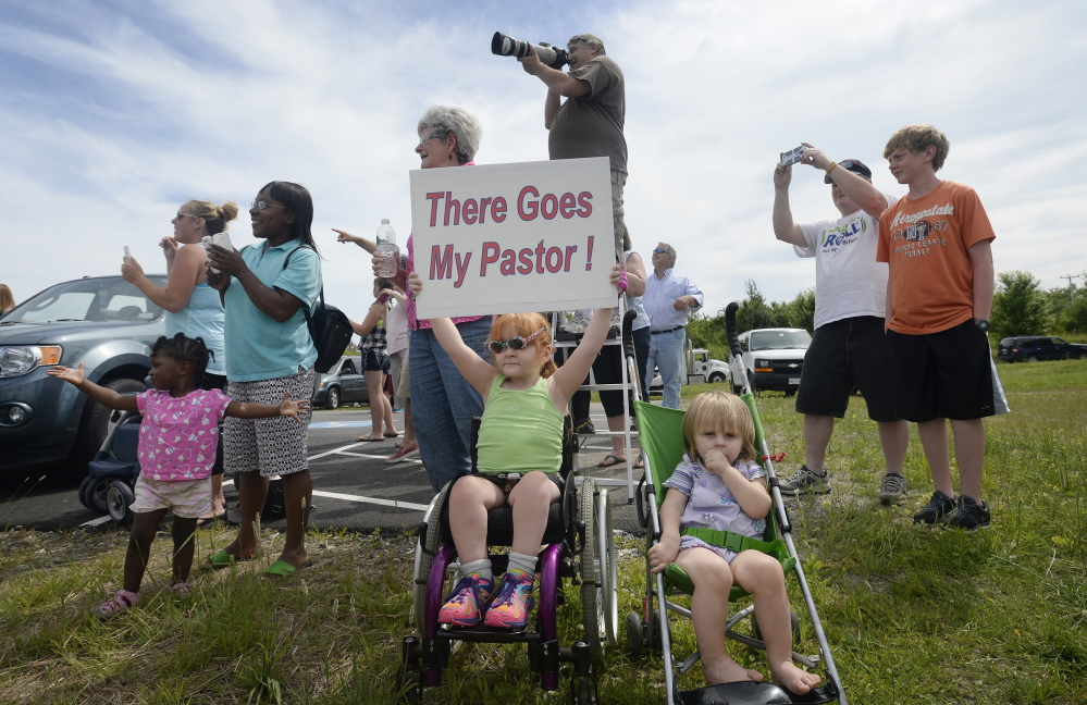 """Four-year-old Sophia Emerson of Biddeford, accompanied by her 1-year-old sister, Natalie, cheers along with other congregants from The Rock Church in Scarborough as their pastor, Lt. Col. Eric Samuelson, made a final flight in an F-15, buzzing the Portland jetport Thursday. Two other F-15 pilots, top left, accompanied him on his """"last mission."""""""