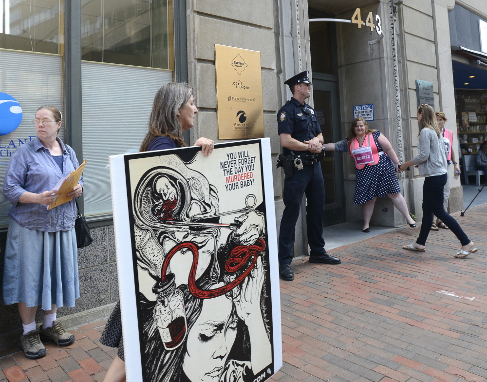 Anti-abortion protester Leslie Sneddon of Richmond, holding her sign, was one of two protesters who showed up on the same side of the street as the Planned Parenthood entrance at 443 Congress St. in Portland on Friday. Another dozen lined up across the street. Planned Parenthood greeters opened the door for clients and staff.