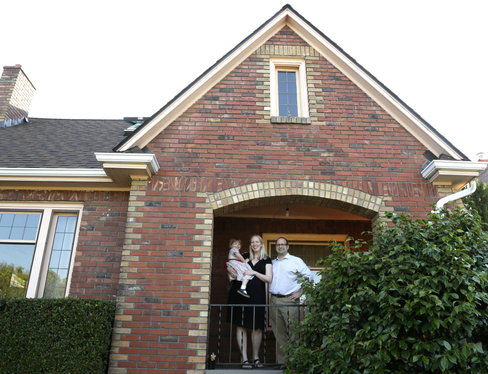 Ryan Carson, right, poses with his wife, Jenny Roraback-Carson, and daughter Clara, 3, at their Seattle home. They are among many would-be home sellers who have mortgage rates so low it doesn't make financial sense to move.