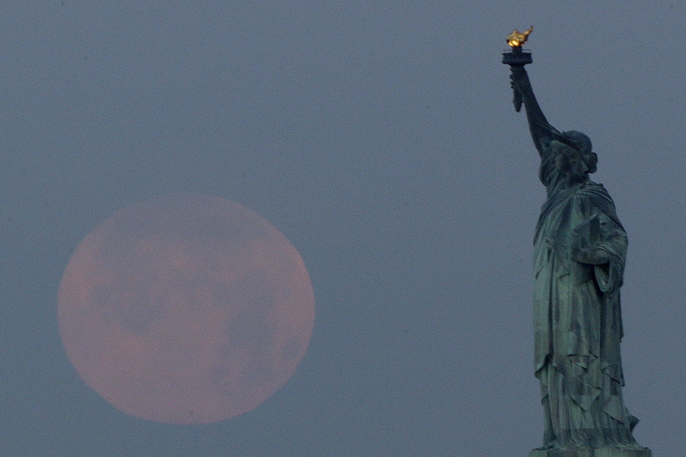 """A """"supermoon"""" sets near the Statue of Liberty on June 23, 2013. A larger-than-normal moon called a supermoon happens Saturday."""