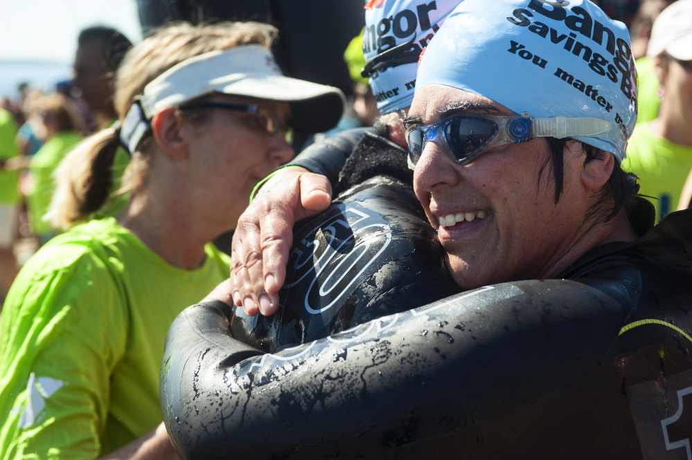 Pattie Demaira hugs her father, Dan Wartenberg, after the Peaks to Portland on Saturday.