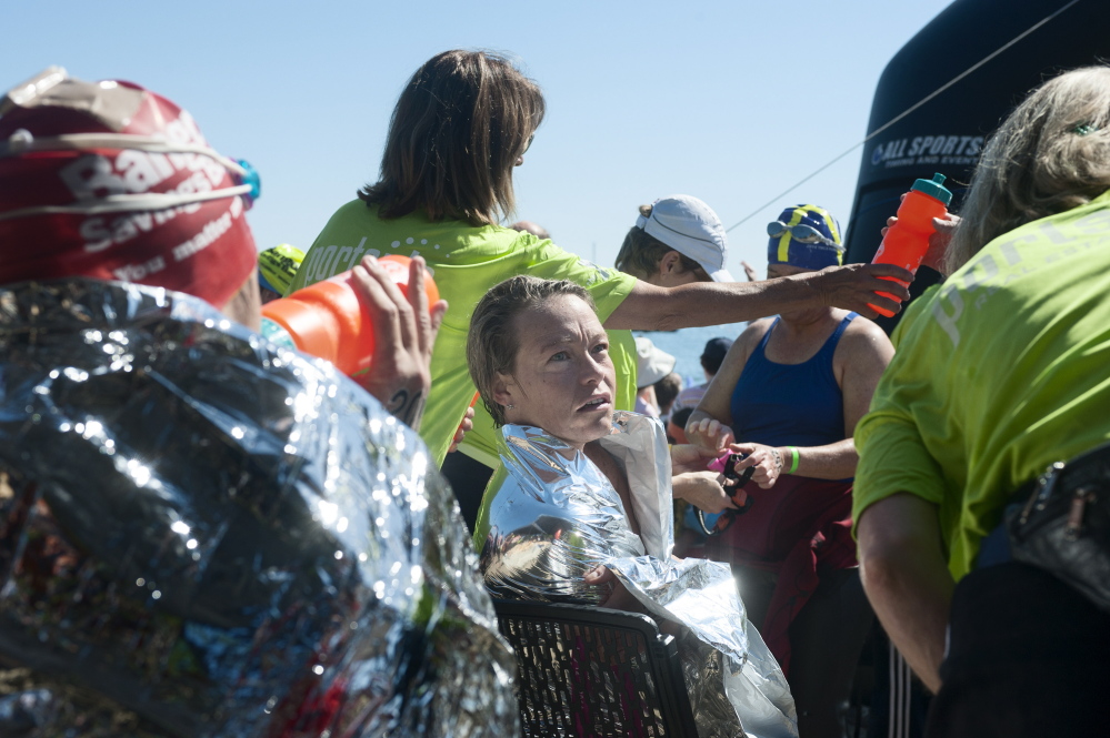 Christie Underwood and other swimmers are given water and thermal emergency blankets to recover after the Peaks to Portland on Saturday.