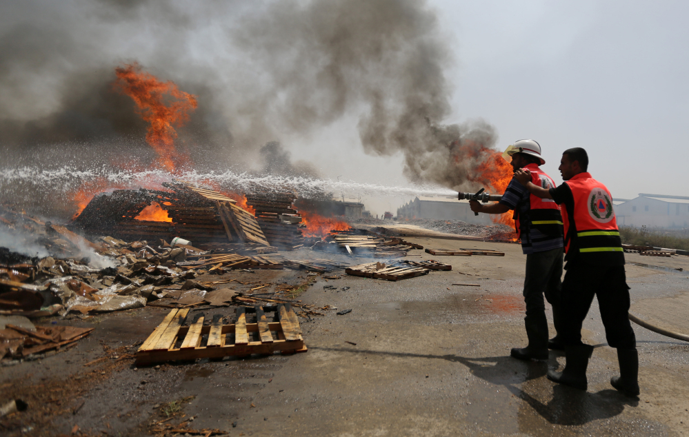 Palestinian firefighters try to extinguish a fire at a cargo terminal at Karni Crossing between Israel and Gaza after it was shelled by Israeli tanks, according to terminal's employees, on Saturday.