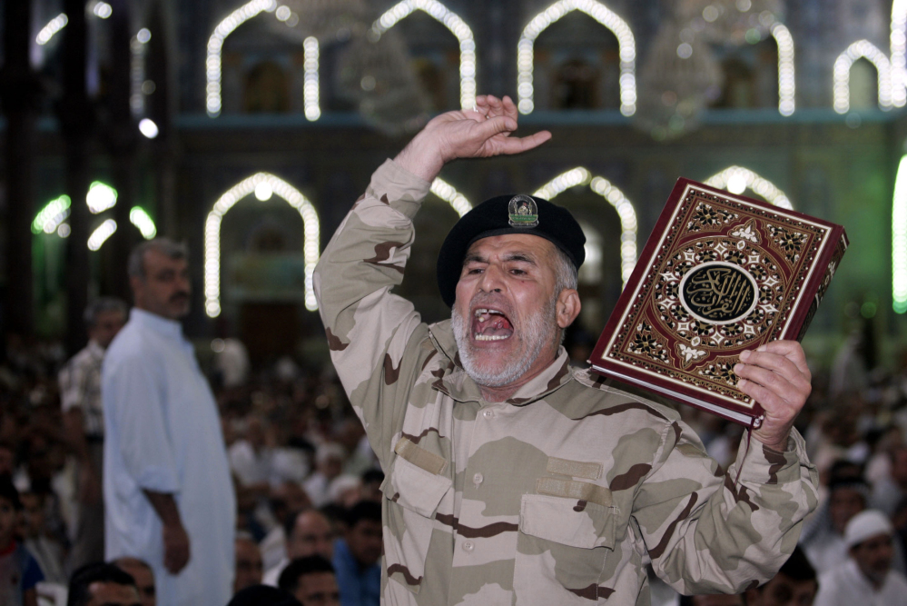 An Iraqi Shiite fighter chants slogans against the al-Qaida-inspired Islamic State group during Friday prayers in the Shiite holy city of Karbala.