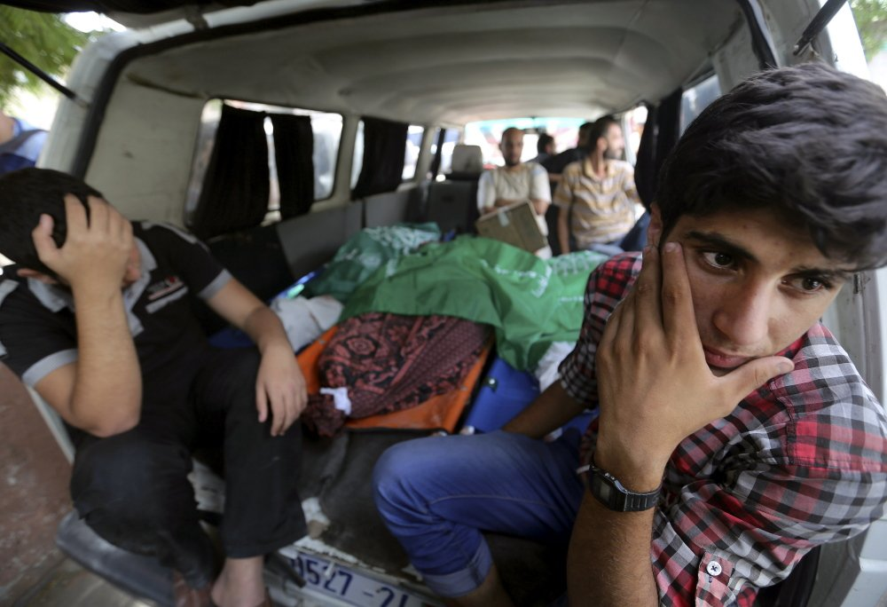 Palestinian mourners wait in a van carrying the bodies of some of the members of the Al-Batsh family who were killed in an Israeli airstrike Saturday, during a funeral procession in Gaza City on Sunday.
