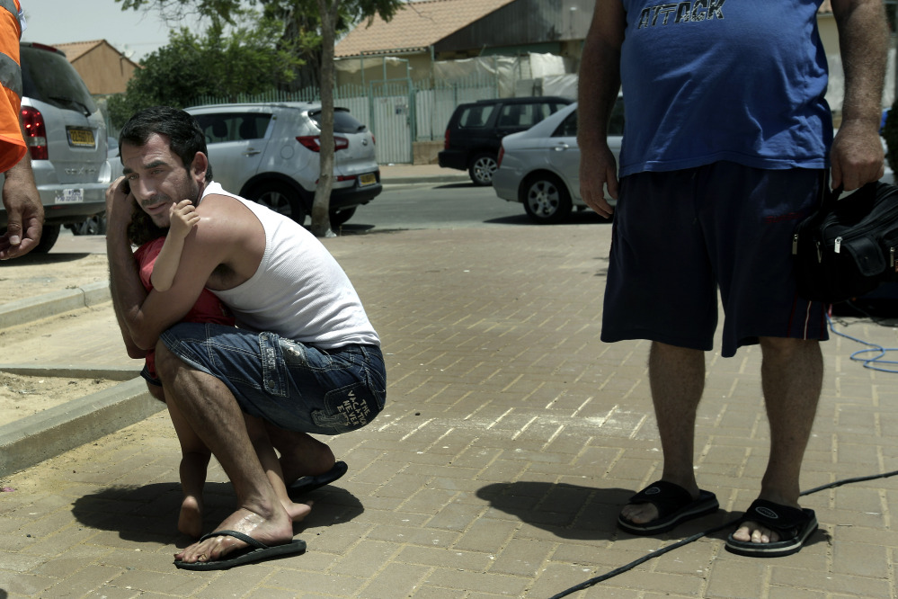 An Israeli hugs his child outside  a shelter as a siren warning of incoming rockets is heard around the southern city of Beersheba, Israel, Saturday.