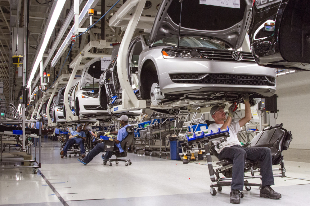 In this July 12, 2013, photo, employees at the Volkswagen plant in Chattanooga, Tenn., work on the assembly of a Passat sedan.