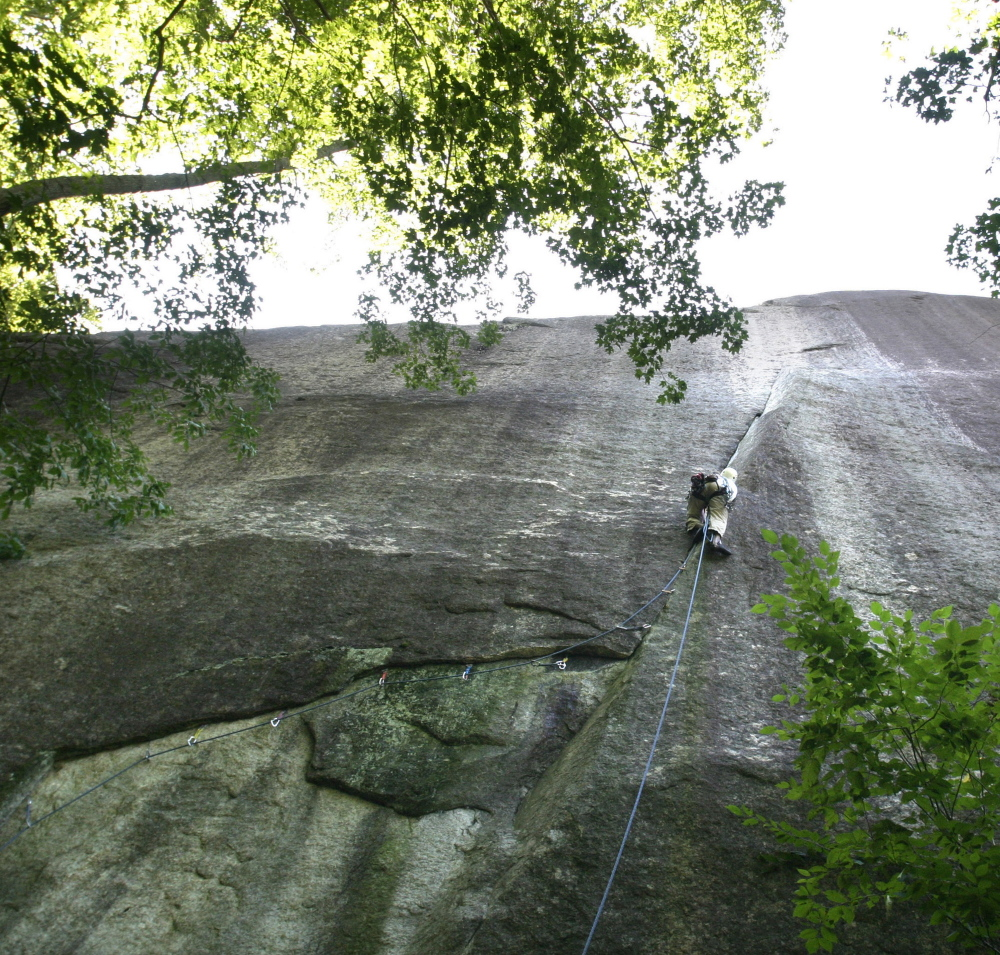 With Cathedral Ledge towering above him, a climber makes his way up a route in Bartlett, N.H. Brian Delaney had been tackling the tough Cathedral Ledge route for years.