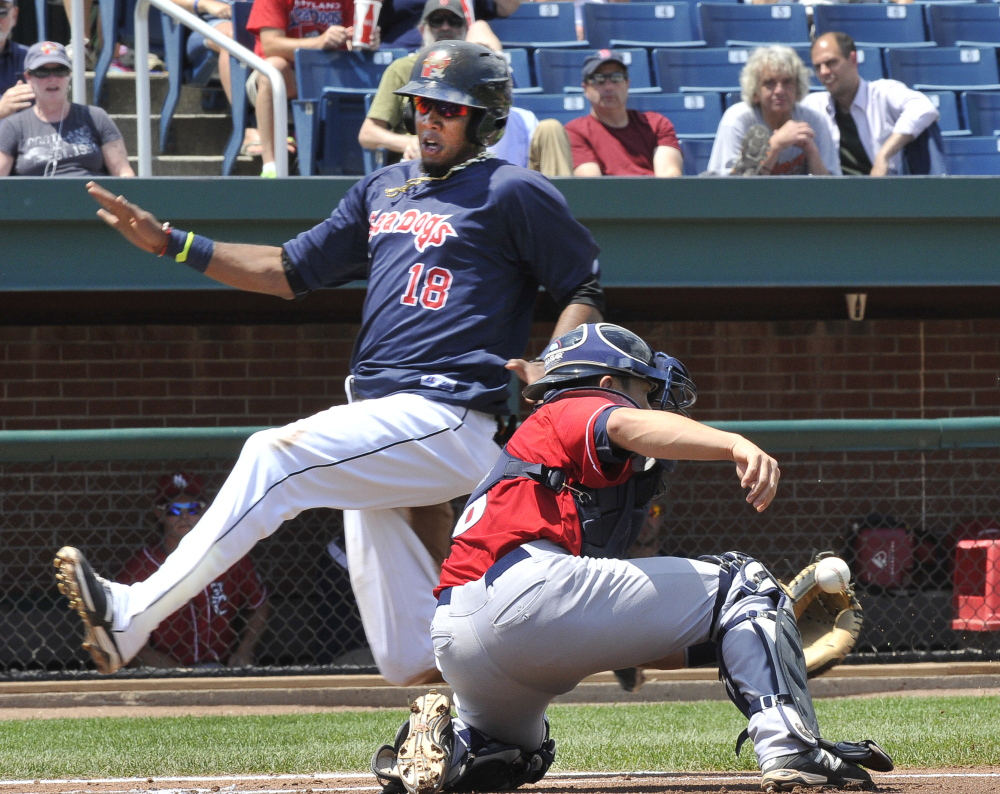 Michael Almanzar of the Portland Sea Dogs slips past catcher Derrick Chung of the New Hampshire Fisher Cats to score on a single by Jonathan Roof in the second inning Monday.
