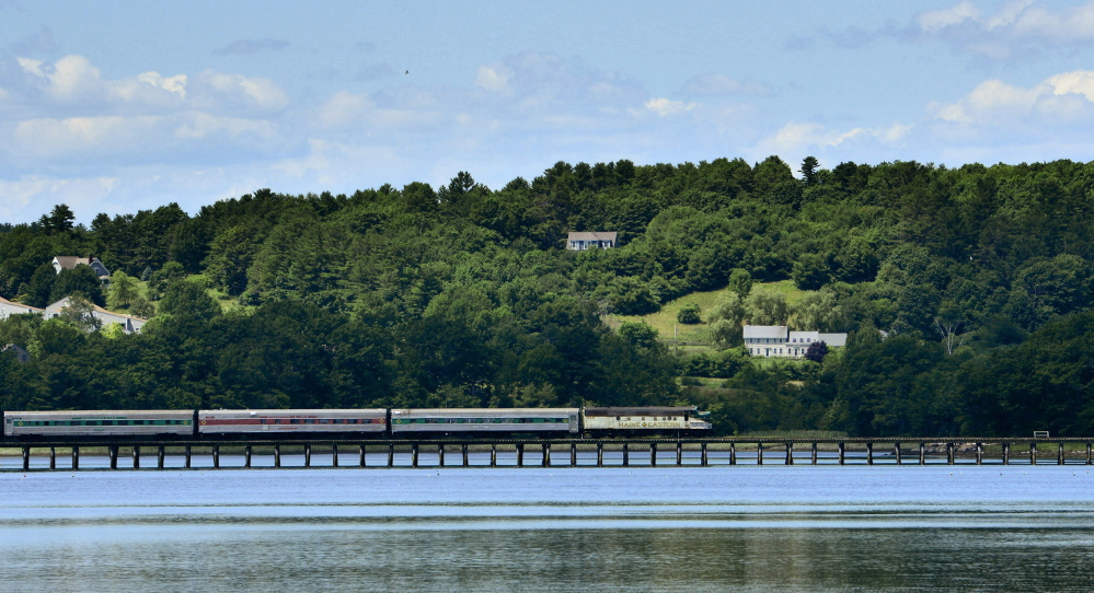 A Maine Eastern Railroad train crosses Friday over the Sheepscot River outside of Wiscasset, which is now the hub of a new train service.