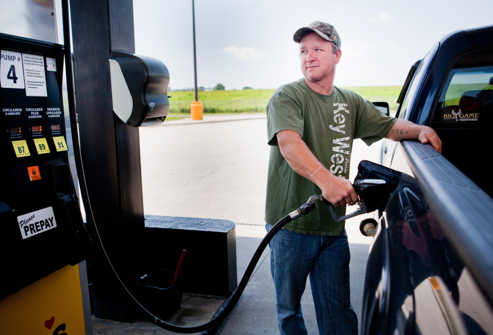 Lance Thompson fills up in Missouri. Fifty-eight percent of people say they're spending more on gas this summer.