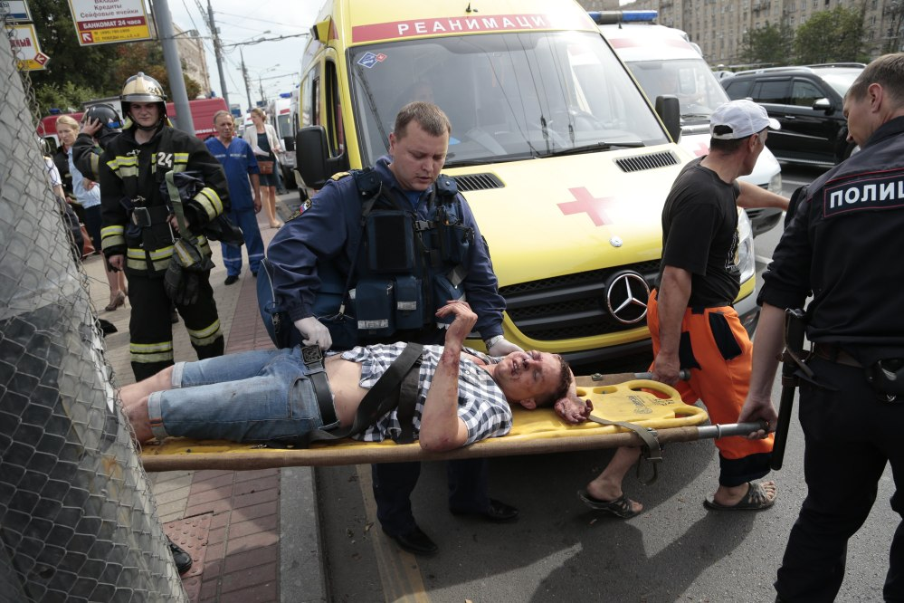 Paramedics and a police officer carry an injured man out from a subway station after a rush-hour subway train derailment in Moscow, on Tuesday. Several cars left the track in the tunnel after a power surge triggered an alarm, which caused the train to stop abruptly.