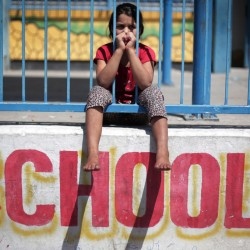 In this Monday photo, a Palestinian girl sits on the wall of the New Gaza United Nations School, where dozens of families have sought refuge after fleeing their home in fear of Israeli airstrikes.