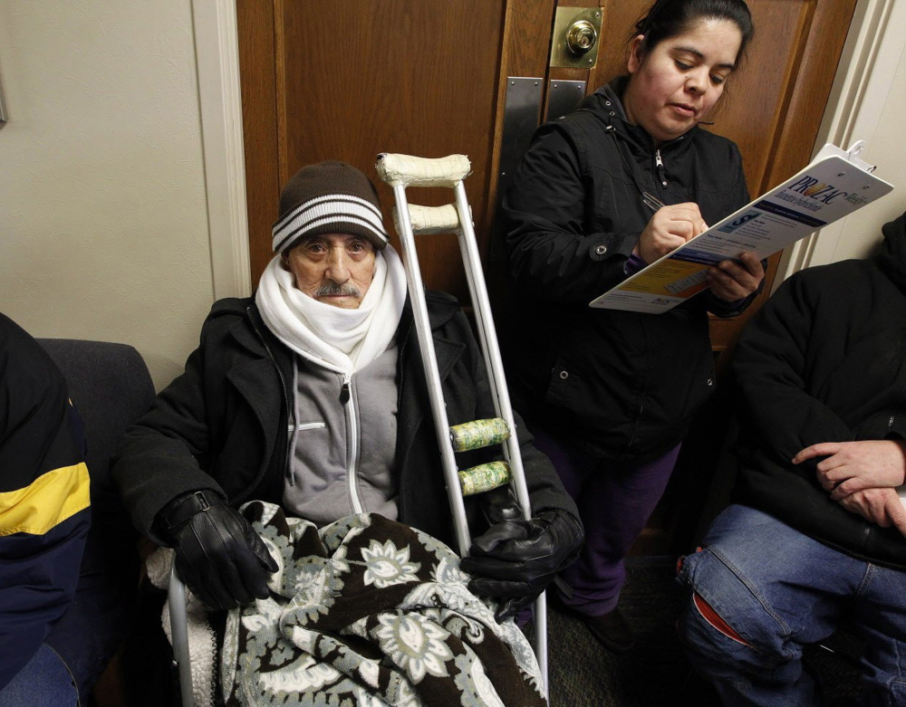 Rosario Cortes, right, helps Jose Real Colin fill out the initial forms to be seen at a faith-based nonprofit organization located in the heart of Milwaukee, where health care for the impoverished is sparse.