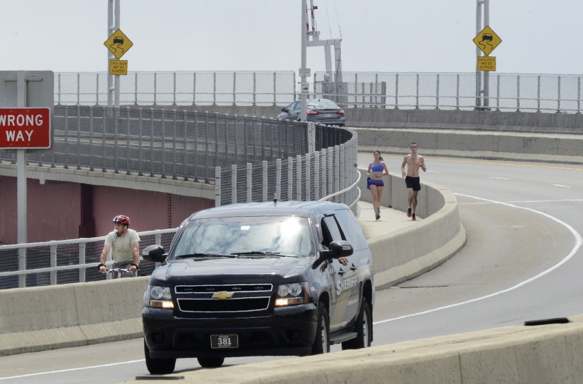 A bicyclist and runners use the barrier-protected sidewalk over the Casco Bay Bridge on Tuesday, with the bike lane marked by a white line alongside vehicle traffic. The Maine DOT says pedestrians who cross the bridge during repairs will have to use bike lanes.